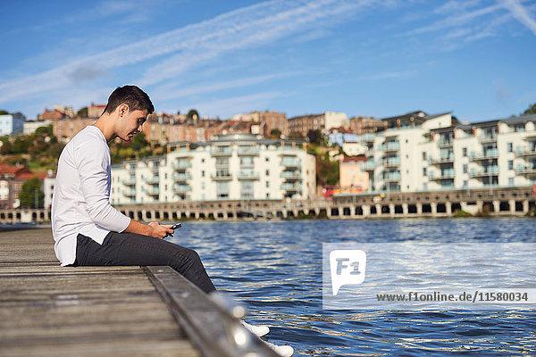 Junger Mann sitzt am Fluss und benutzt ein Smartphone  Bristol  UK