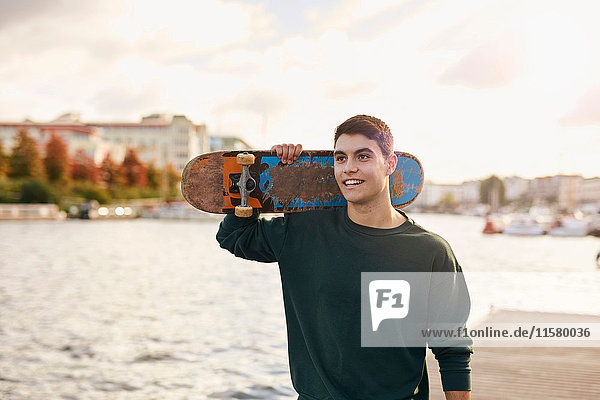 Junger Mann geht am Fluss entlang und trägt ein Skateboard  Bristol  UK
