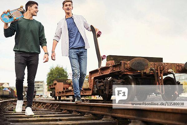 Zwei junge Männer gehen mit Skateboards entlang einer Zugstrecke  Bristol  UK