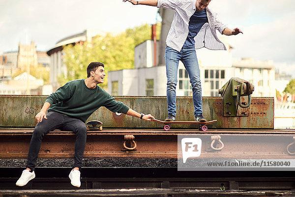 Zwei junge Männer beim Herumtollen auf Zuggleisen  balancieren auf Skateboard Bristol  UK