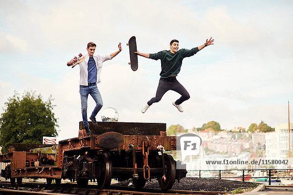 Zwei junge Männer springen auf Zuggleisen vom Anhänger  Bristol  UK