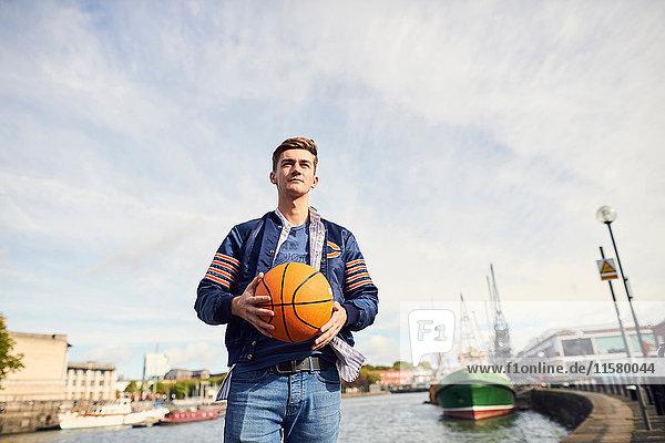 Junger Mann am Fluss  hält Basketball  Bristol  UK