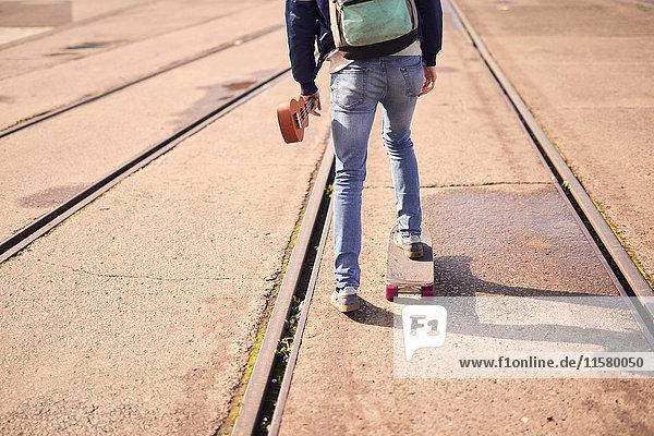 Junger Mann fährt Skateboard zwischen den Fahrgassen  Rückansicht  niedriger Abschnitt  Bristol  UK