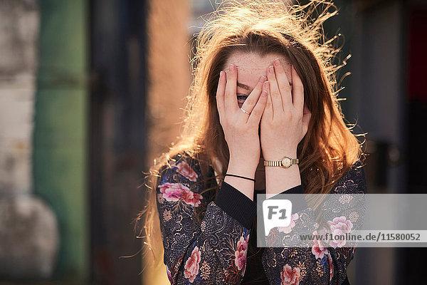Porträt einer jungen Frau  die ihr Gesicht mit Händen bedeckt  Bristol  UK