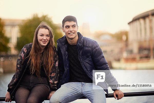 Porträt von zwei Freunden  auf einer Reling am Fluss sitzend  Bristol  UK