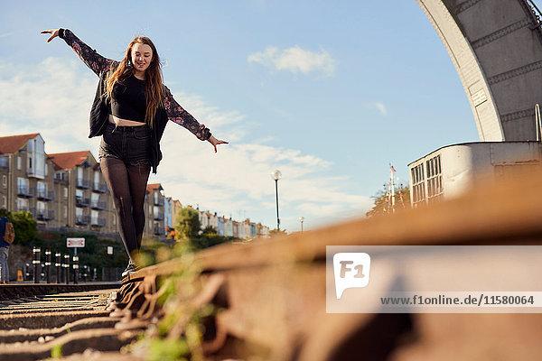 Junge Frau beim Balancieren auf Zuggleisen  Blick aus niedrigem Winkel  Bristol  UK