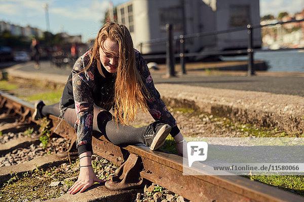 Junge Frau beim Spagat  Balancieren auf Zuggleisen  Bristol  UK