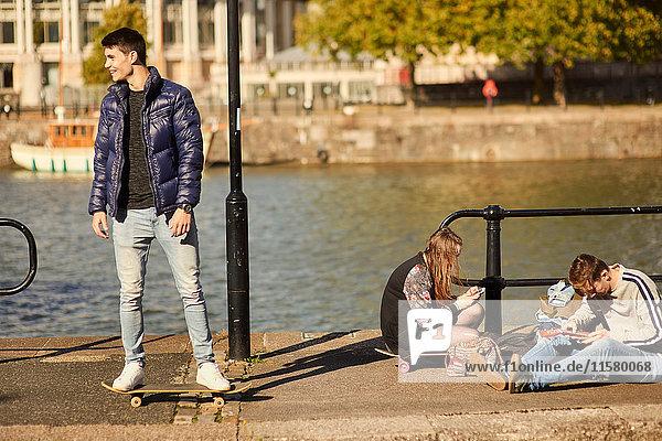 Drei Freunde treiben sich am Fluss herum  junger Mann auf Skateboard  Bristol  UK
