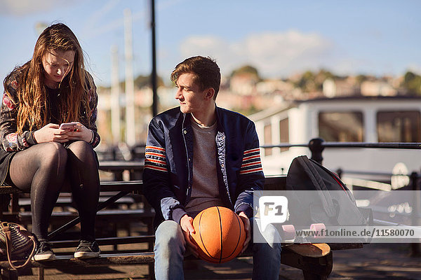 Zwei Freunde sitzen im Freien  junger Mann hält Basketball  junge Frau benutzt Smartphone  Bristol  UK