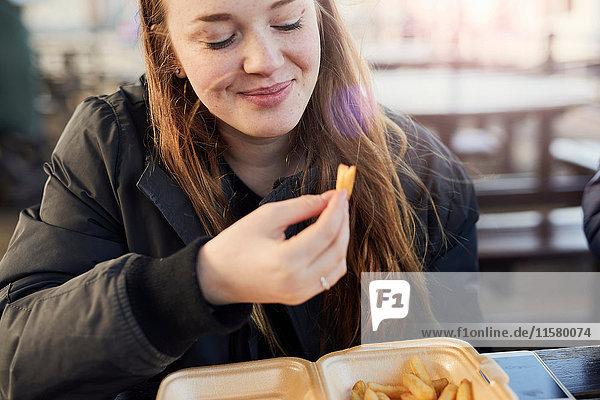 Porträt einer jungen Frau  im Freien  Chips essend  Bristol  UK