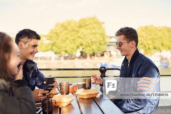 Drei Freunde  sitzen im Freien und trinken heiße Getränke  Bristol  UK