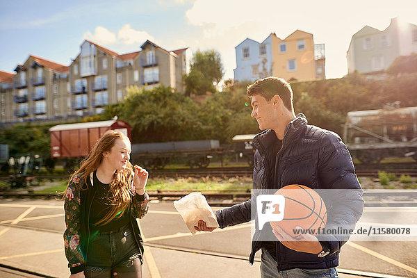 Junger Mann teilt eine Tüte Chips mit einem Freund  junger Mann hält Basketball  Bristol  UK
