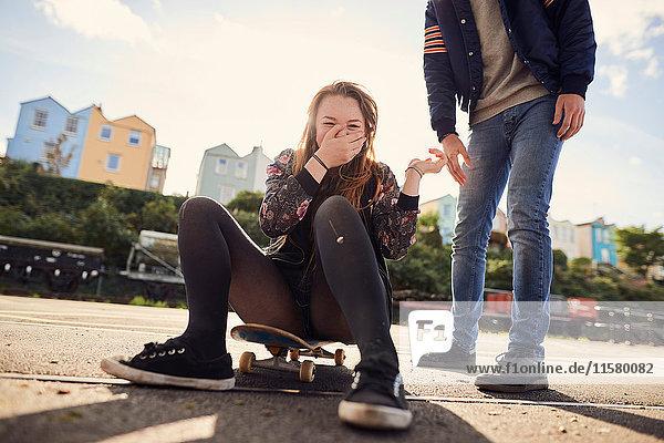 Zwei Freunde albern im Freien herum  junge Frau sitzt auf einem Skateboard  lachend  niedrige Sektion  Bristol  UK