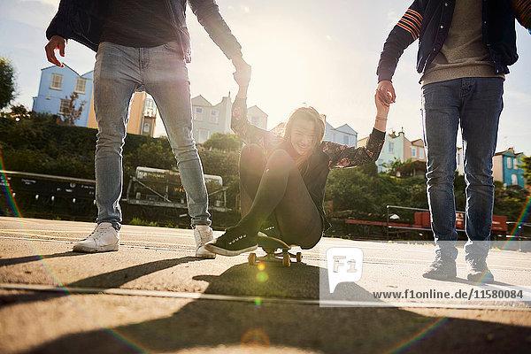 Drei Freunde treiben sich im Freien herum  junge Männer ziehen junge Frau auf dem Skateboard mit  Bristol  UK