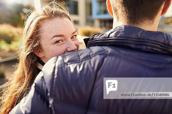 Zwei Freunde gehen im Freien  junge Frau schaut über die Schulter  Rückansicht  Bristol  UK