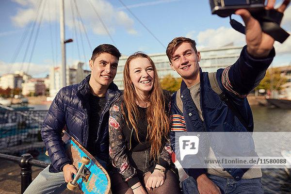 Drei Freunde sitzen draussen und fotografieren sich selbst mit der Kamera  Bristol  UK
