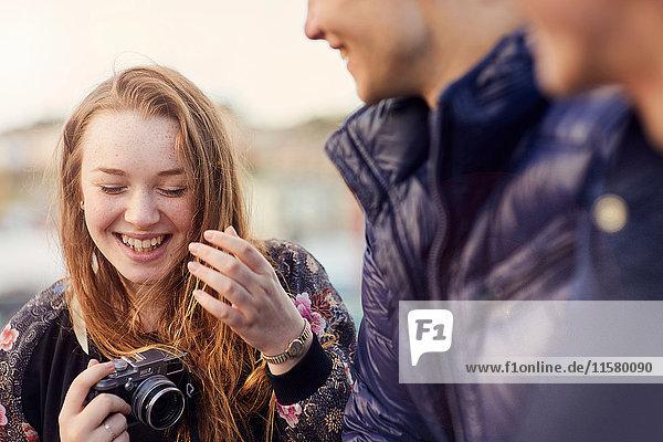 Drei Freunde im Freien  junge Frau mit Kamera in der Hand  lachend  Bristol  UK
