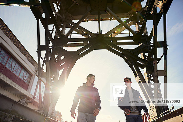 Zwei junge Männer gehen unter einer Brücke hindurch  Bristol  UK