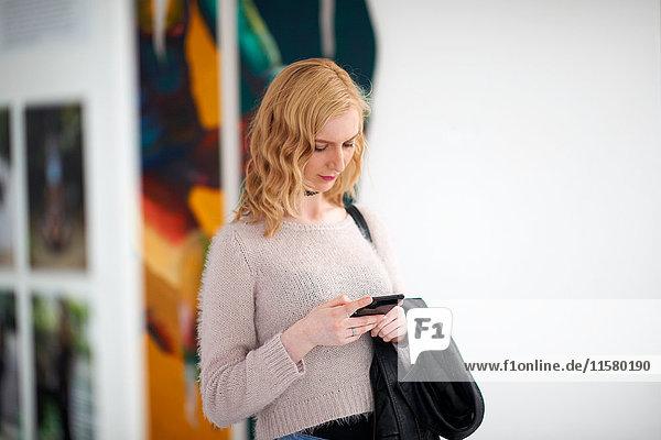 Junge Frau schaut auf Smartphone