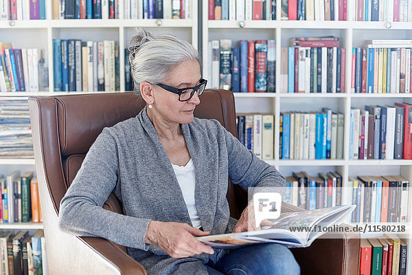 Senior woman sitting in chair in library  reading book