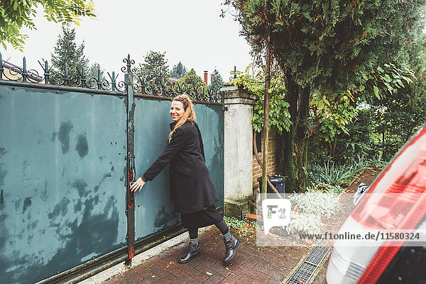 Young woman closing driveway gates