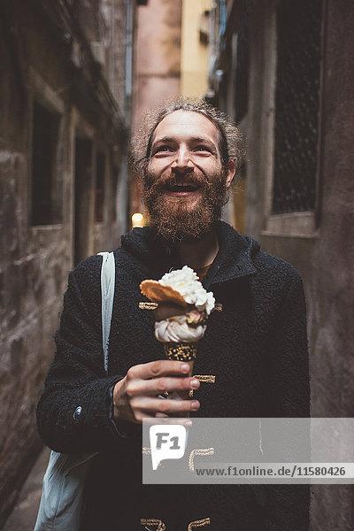Mittelgroßer erwachsener Mann mit Gelato in dunkler Gasse  Venedig  Italien