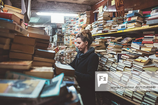 Young woman browsing in stacked book shop  Venice  Italy