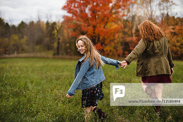 Mother and daughter holding hands walking in meadow  Lakefield  Ontario  Canada