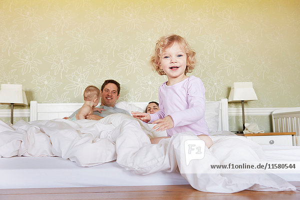 Portrait of cute female toddler sitting on bed with parents and baby sister