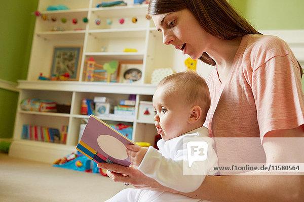 Mittelgroße erwachsene Frau und kleine Tochter lesen Märchenbuch im Spielzimmer