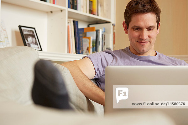Mid adult man sitting on sofa looking at laptop