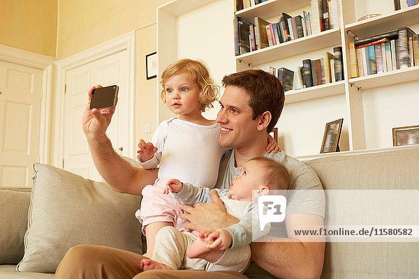 Mittelgroßer erwachsener Mann nimmt Smartphone-Selfie mit Kleinkind und Baby-Tochter auf Sofa