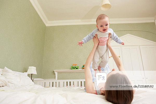 Frauen liegen im Bett und halten ihre Tochter hoch