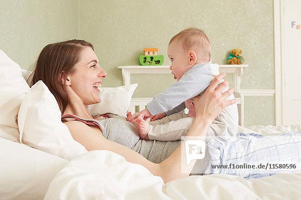Frauen liegen im Bett und spielen mit der kleinen Tochter