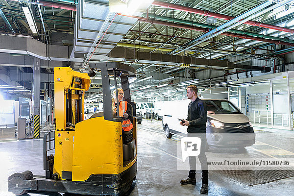 Apprentice engineer with forklift truck in car factory