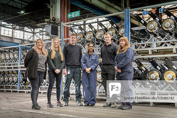 Gruppenporträt von männlichen und weiblichen Auszubildenden in einer Autofabrik
