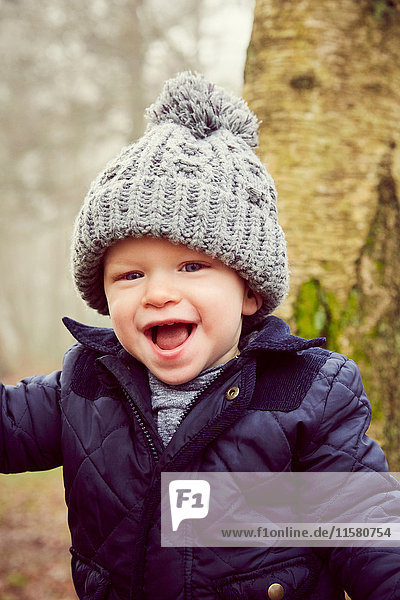 Portrait of male toddler in knitted hat in forest