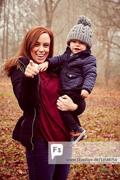 Mid adult woman carrying toddler son and pointing in autumn forest