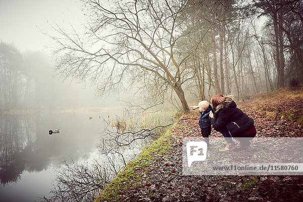 Mid adult woman crouching with toddler son on misty riverbank