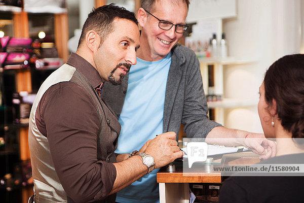 Männliche Friseure beraten Kunden über Frisur im Salon