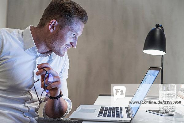 Junger Geschäftsmann arbeitet spät am Schreibtisch und schaut auf den Laptop