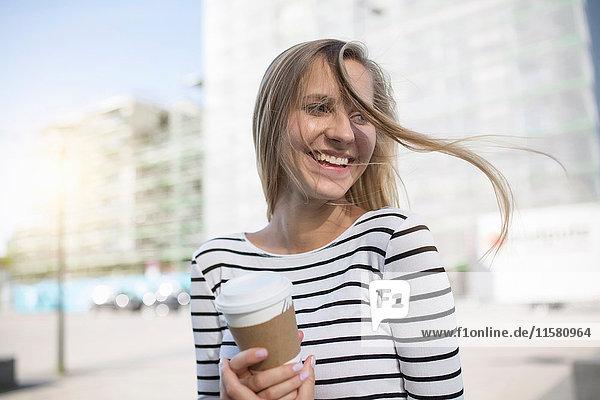 Junge Frau mit blonden Fliegehaaren mit Kaffee zum Mitnehmen