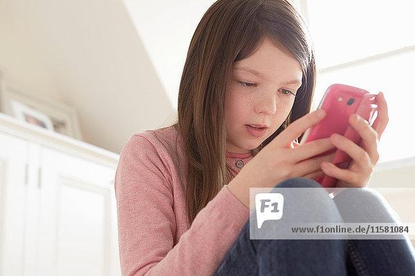 Mädchen sitzt und schaut auf Smartphone