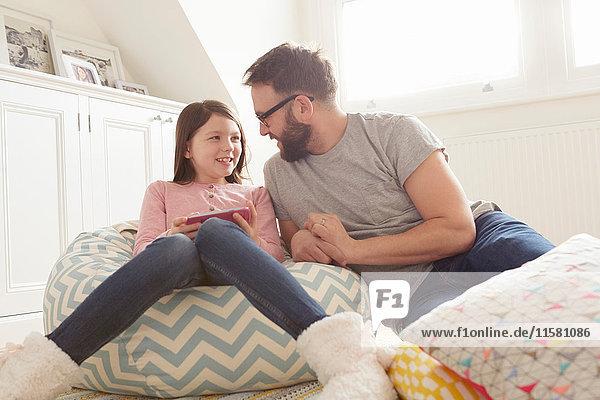 Mittelgroßer erwachsener Mann und Tochter auf Sitzsackstuhl liegend