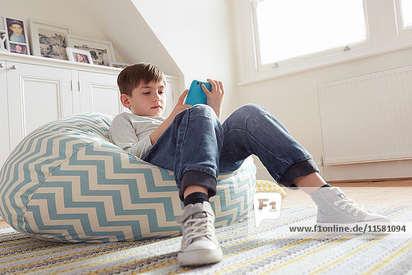 Boy reclining on beanbag chair looking at digital tablet