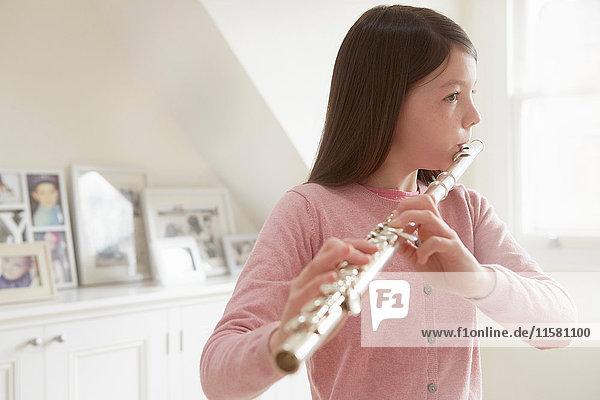 Mädchen übt Flöte im Wohnzimmer