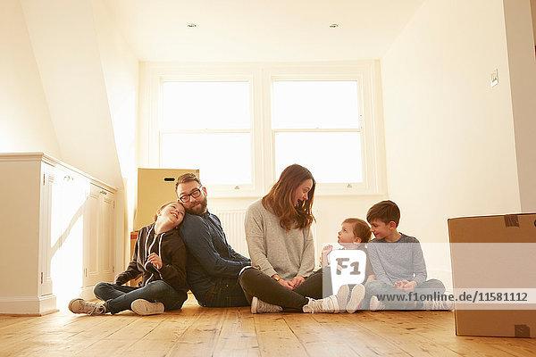 Mittleres erwachsenes Paar und drei Kinder sitzen auf dem Boden in einem neuen Heim.