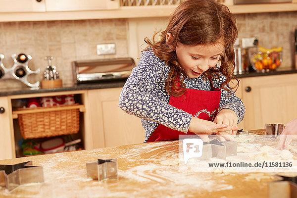 Mädchen backt sternförmiges Gebäck am Küchentisch