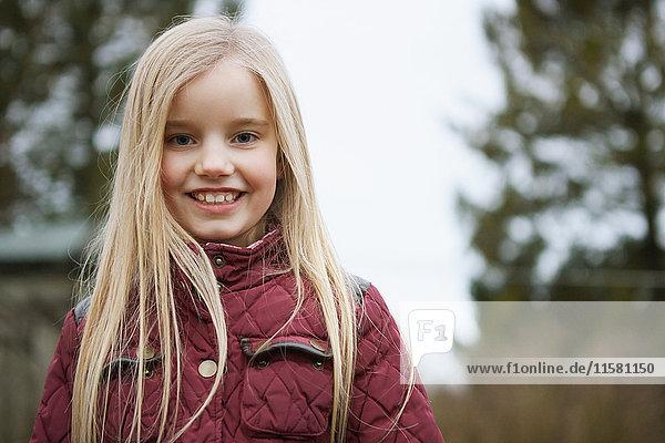 Bildnis eines Mädchens mit langen blonden Haaren im Freien