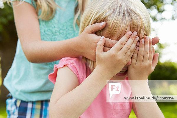 Abgeschnittene Aufnahme eines Mädchens mit Händen  die die Augen eines Freundes im Garten bedecken.